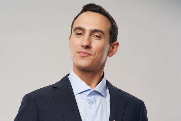 Uomo d'affari in camicia e giacca su sfondo grigio sguardo fiducioso modello ritratto