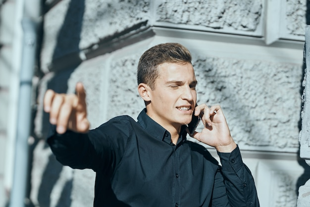 Uomo d'affari in una camicia vicino all'edificio con i documenti nelle sue mani. foto di alta qualità