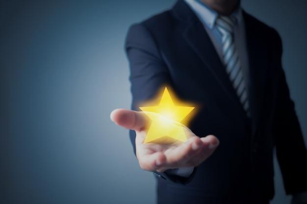 Uomo di affari che mostra valutazione a stelle o obiettivo su blu scuro