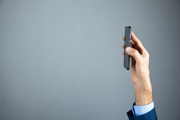 L'uomo d'affari mostra il telefono in mano