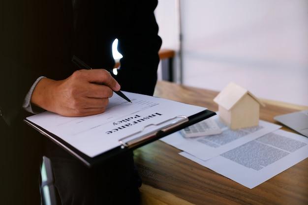 Uomo d'affari che firma contratto fare un affare con agente immobiliare concetto per consulente e concetto di assicurazione casa.