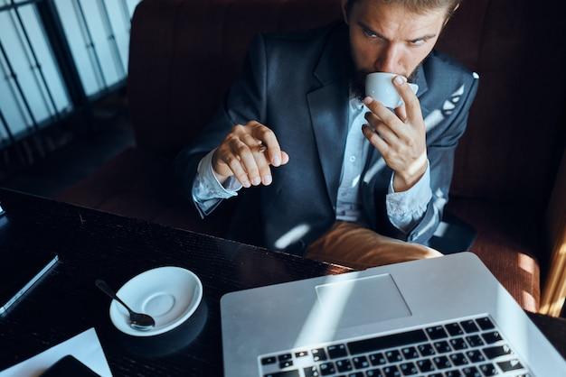 Uomo d'affari seduto in un bar davanti a un computer portatile con una tazza di caffè lavoro tecnologia lifestyle.