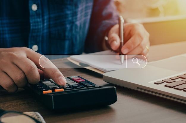 Uomo d'affari seduto alla ricerca di persone che pagano le tasse annuali insieme al calcolo con una calcolatrice per registrarlo come prova