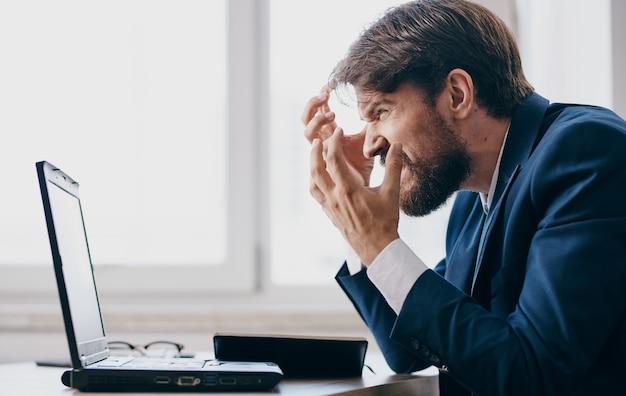 Uomo d'affari seduto a un tavolo in un vestito davanti a un manager di ufficio di emozioni del computer portatile. foto di alta qualità Foto Premium