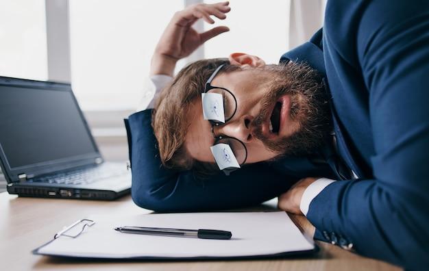 Uomo di affari che dorme sul lavoro con gli occhiali con fogli di carta Foto Premium
