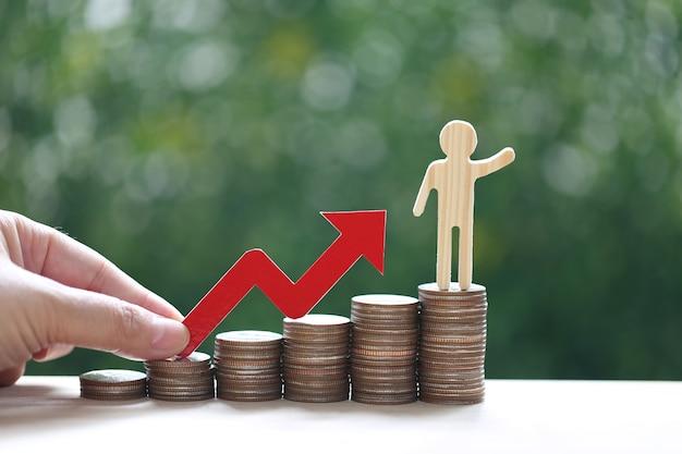 Uomo d'affari su una pila di monete soldi con la mano che tiene il grafico a freccia rossa su sfondo verde naturale, investimento e concetto di affari