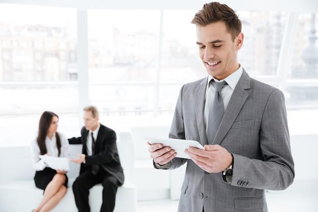 Uomo d'affari in piedi con laptop in ufficio con partner commerciali sul divano