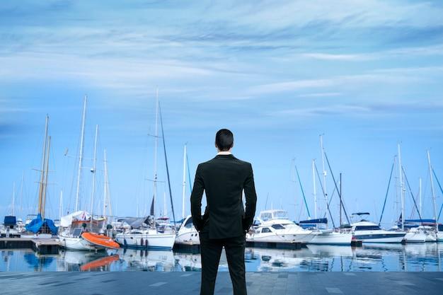 Uomo d'affari in piedi allo yacht club