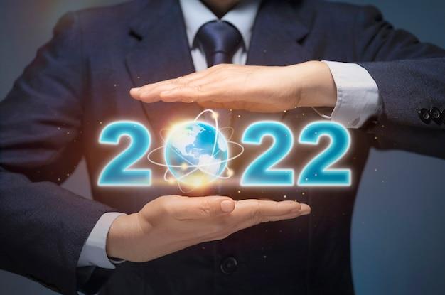 L'uomo d'affari avvia l'attività nel 2022. l'uomo d'affari tiene la mappa del mondo e il 2022 mostra il felice anno nuovo 2022, l'obiettivo aziendale, il piano futuro, il piano del nuovo anno, l'obiettivo del successo aziendale, il concetto di crescita economica mondiale.