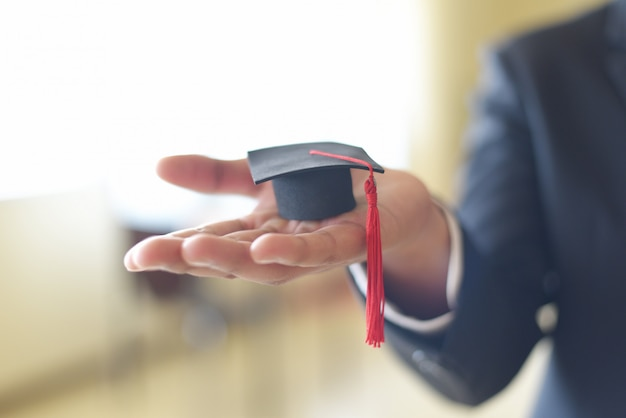 L'uomo o lo studente di affari con il cappuccio di graduazione a disposizione nella graduazione del giorno si è congratulato con i laureati in università - concetto di studio di affari di istruzione di graduazione