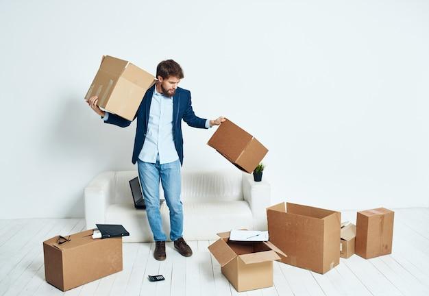 Uomo d'affari in un vestito scatole nelle mani raccogliendo le cose in movimento
