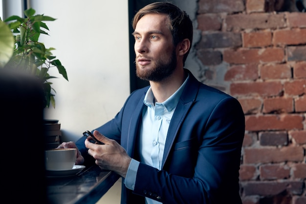 Uomo d'affari in un vestito di un funzionario del caffè che parla al telefono