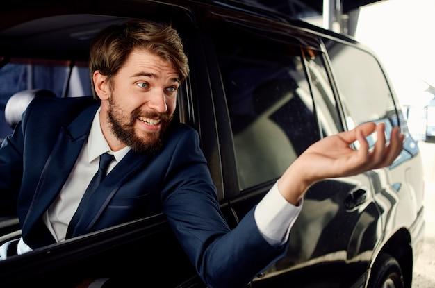 Uomo d'affari in tuta guida auto in showroom ed emozioni modello