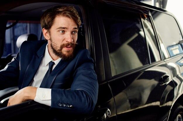 Uomo d'affari in tuta guida auto in showroom e modello di emozioni.