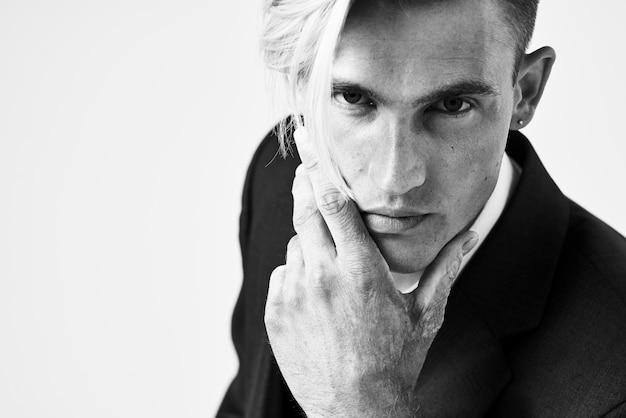Uomo d'affari in un'acconciatura alla moda del vestito che posa foto in bianco e nero di stile moderno