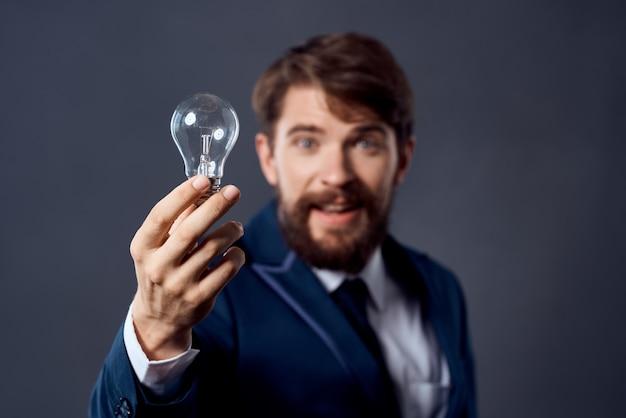 Uomo d'affari in un vestito che tiene una strategia di idea di tecnologia della lampada