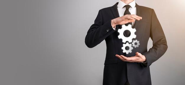 Uomo d'affari in tuta che tiene ingranaggi in metallo e meccanismo di ruote dentate che rappresenta il concetto di lavoro di squadra di interazione, gruppo di tenuta in mano di ruota dentata virtuale.