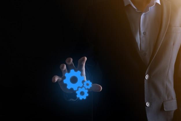 Uomo di affari in vestito che tiene gli ingranaggi del metallo e il meccanismo delle ruote dentate che rappresentano il lavoro di squadra di interazione