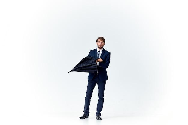 Uomo d'affari in un vestito che tiene un ombrello stile elegante protezione dalla pioggia. foto di alta qualità