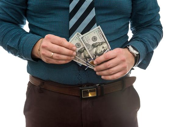 Uomo di affari in vestito che ci tiene le fatture del dollaro, isolate su bianco.