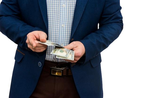 Uomo di affari in vestito che ci tiene le fatture del dollaro, isolate su bianco