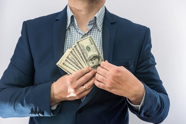 L'uomo d'affari in giacca e cravatta tiene dollari, molti soldi, isolati. concetto di finanza