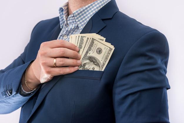 L'uomo d'affari in un vestito tiene dollari, un sacco di soldi, isolato. concetto di finanza