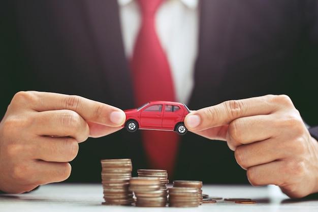 Uomo d'affari in tuta mano aperta puntellare il modello di abbraccio di auto giocattolo su un sacco di soldi del prestito assicurativo moneta impilata