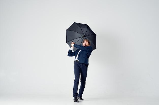 Uomo d'affari in un vestito in posa su uno spazio luminoso con un ombrello nero in mano