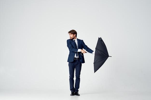 Uomo d'affari in un vestito in posa su una luce con un ombrello nero in mano