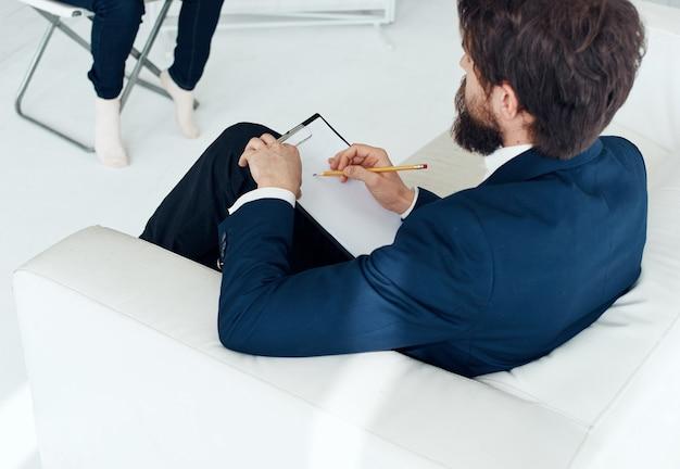 Un uomo d'affari in giacca e cravatta si siede su un divano bianco in una stanza luminosa, vista laterale. foto di alta qualità