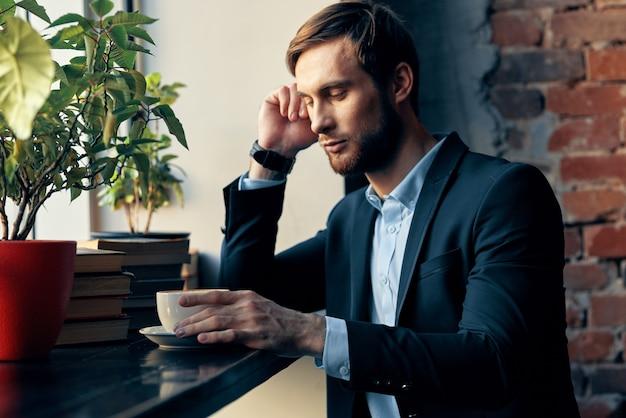 Uomo d'affari in vestito che si siede nel professionista di stile di vita della colazione del caffè