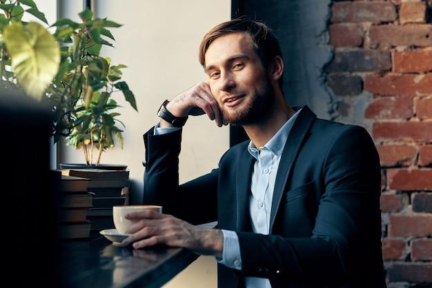 Uomo di affari in un vestito che si siede in una colazione di svago del lavoro del caffè