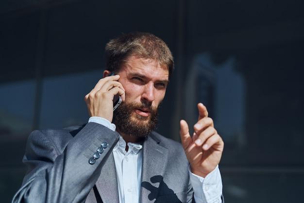 Uomo d'affari in un vestito a parlare al telefono all'aperto direttore aziendale esecutivo