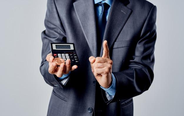 Uomo d'affari in un vestito con monete in mano e una calcolatrice dei tassi di cambio.