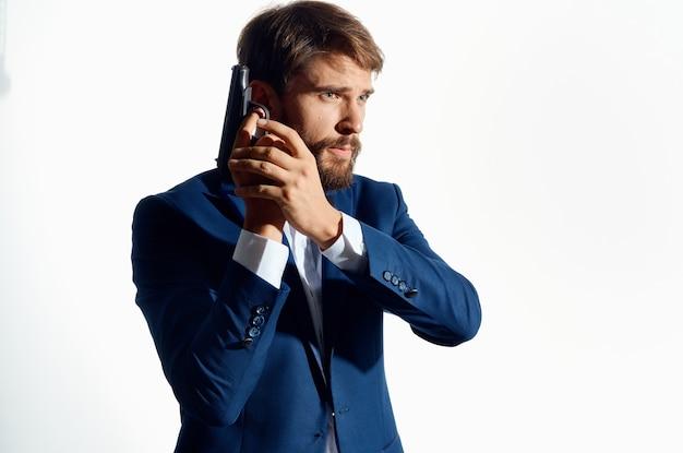 Uomo d'affari in giacca e cravatta con una pistola in mano crimine di cautela detective.