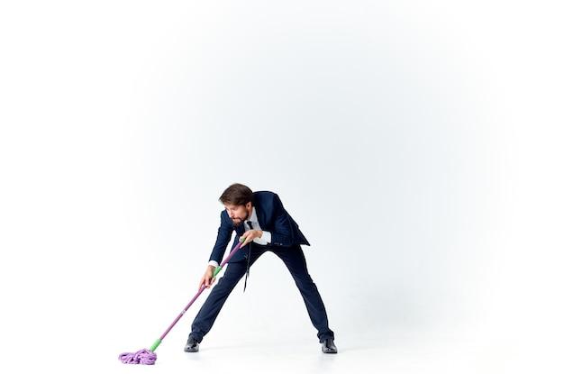Uomo d'affari in giacca e cravatta con una scopa in mano che fornisce servizi di pulizia dei pavimenti. foto di alta qualità