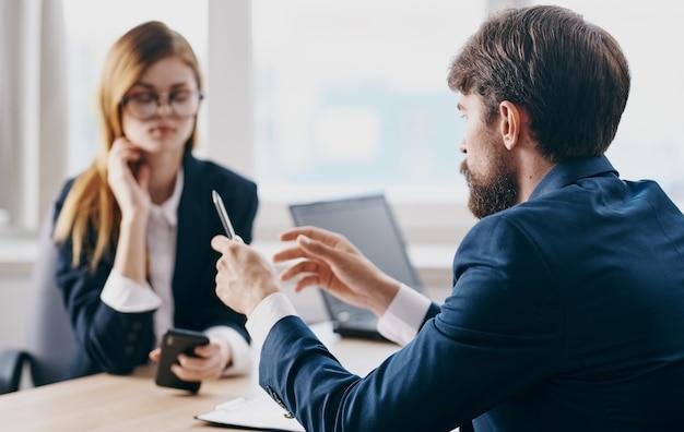 Un uomo d'affari in giacca e cravatta e una donna comunicano al lavoro uno di fronte all'altro al tavolo in ufficio. foto di alta qualità