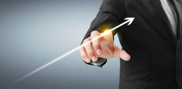 Uomo d'affari che tocca un design digitale di una freccia che sale