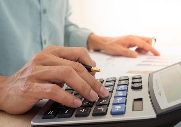 Uomo di affari che per mezzo di un calcolatore per calcolare le spese dalle entrate disposte sul tavolo