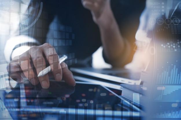 Uomo d'affari che utilizza tablet digitale analizzando i dati di vendita con grafico finanziario sullo schermo virtuale