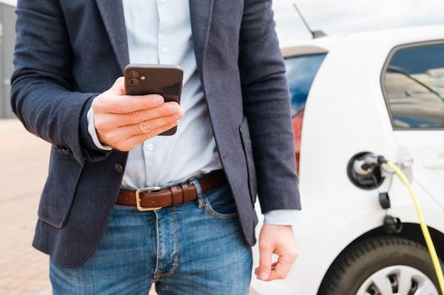 Uomo d'affari utilizzando un telefono cellulare e ricarica auto elettrica al punto di ricarica