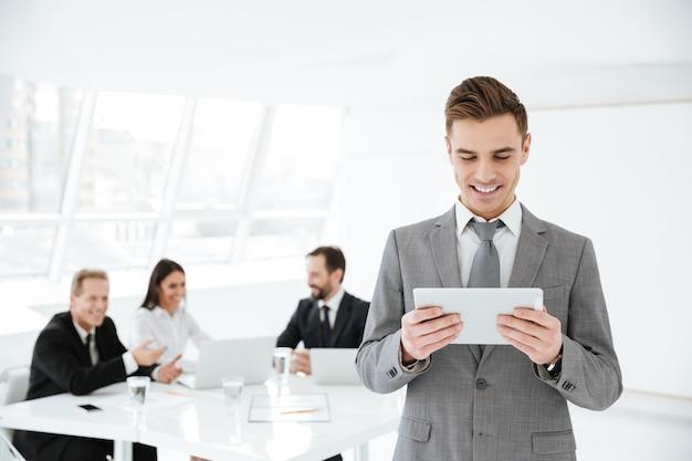 Uomo d'affari che utilizza computer tablet in ufficio con i colleghi