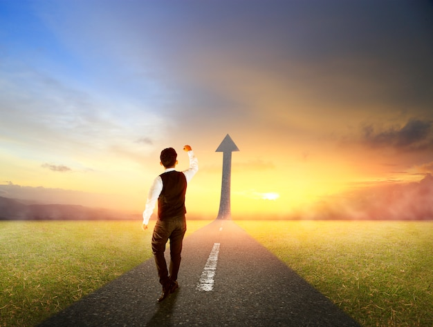Uomo d'affari che cammina sulla strada statale salendo come una freccia per il successo