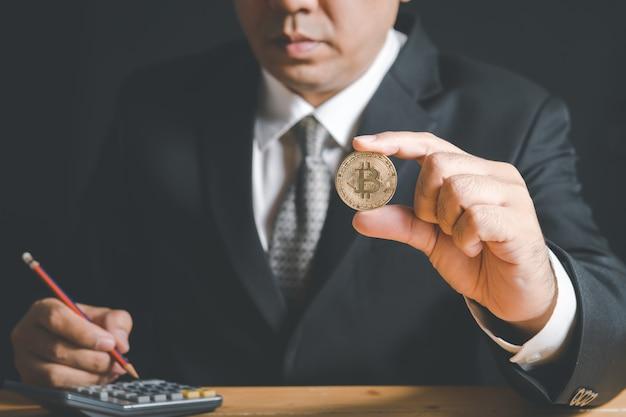 Uomo d'affari che indossa tuta e cravatta tenendo bit moneta su sfondo nero, denaro virtuale elettronico per il web banking e il pagamento di rete internazionale,