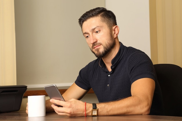 Uomo d'affari con tazza e cellulare in mano seduto al tavolo