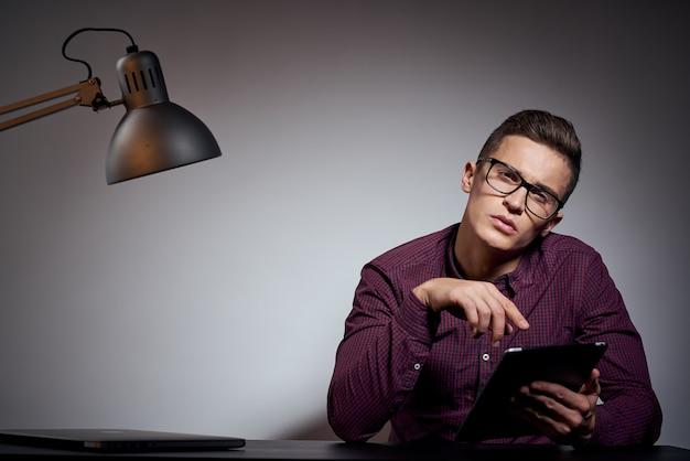 Uomo d'affari con gli occhiali e una maglietta seduto a un tavolo