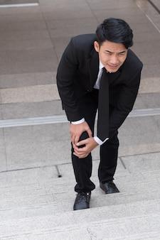 Uomo d'affari con dolore al ginocchio, concetto di ostacolo