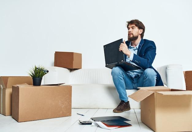 Uomo di affari con il computer portatile che si siede sul divano disimballaggio delle scatole ufficiale foto di alta qualità