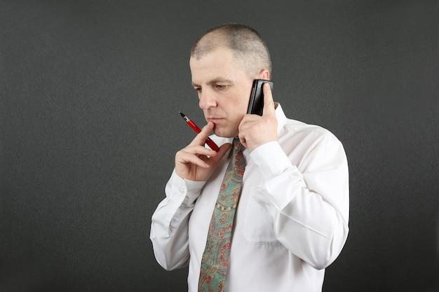 Uomo d'affari con penna e telefono cellulare